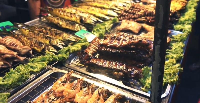 Тайская еда. Огромный ассортимент всевозможных шашлыков и барбекю, из разных видом мяса в Тайланде на ночном рынке в Панган
